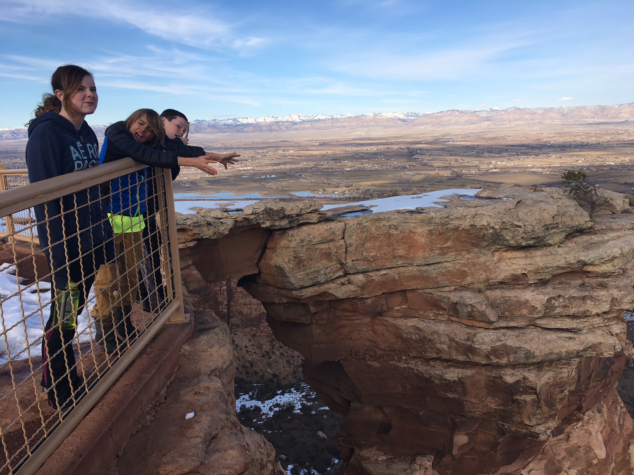 kids at window rock viewpoint looking down into wedding and lizard canyons in winter
