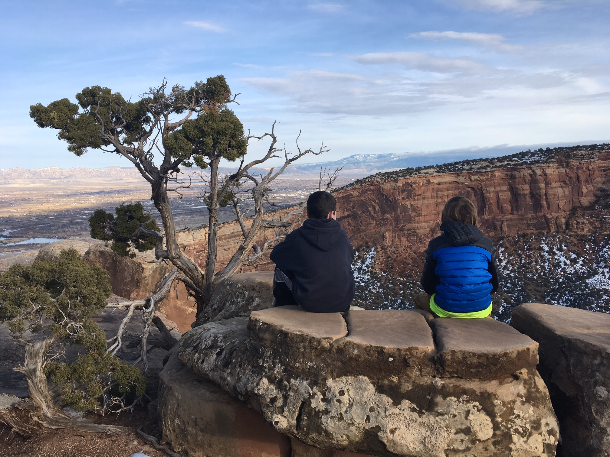 two children sitting on the edge of wedding canyon in winter window rock trail bookcliff view shelter colorado national monument