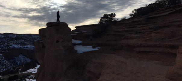 boy standing on the saddlehorn formation, colorado national monument