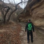 matt janson hiking under a boulder in echo canyon colorado national monument